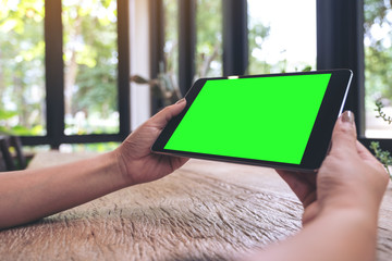 Mockup image of hands holding black tablet pc with blank screen on vintage wooden table