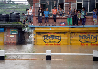 People gather on the balcony of a house submerged in the flooded neighborhood after incessant rainfall in Bhaktapur