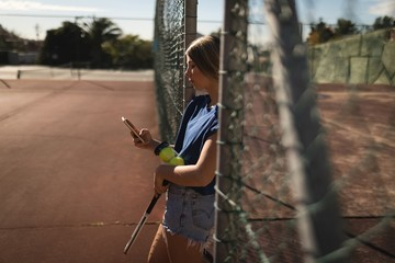 Woman using mobile phone in the tennis court