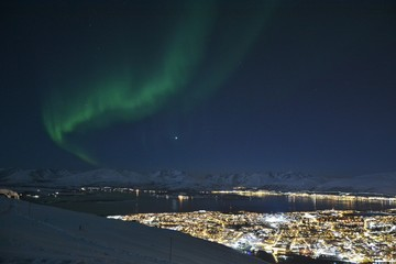 The northern lights (Aurora Borealis) and the city scape from Fjellheisen Peak over the city