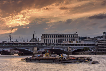 The river Thames, London, set against a dramatic red and orange sunset. There is a working barge in the foreground of the image