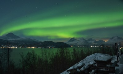 The northern lights (Aurora Borealis) over Seljelvnes, Troms by the sea and the snowy mountains
