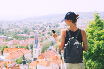 Woman with smartphone in hand on background of Ljubljana City, Slovenia, Europe