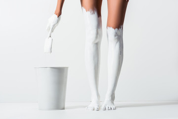 cropped image of woman with legs painted with white paint holding brush above bucket on white
