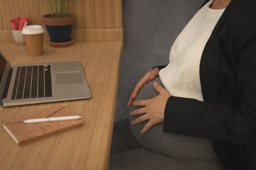 Pregnant businesswoman touching her belly at desk