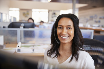 Young mixed race woman in a call centre looking to camera