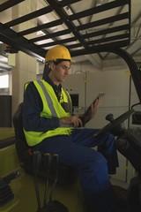 Male worker using digital tablet in forklift