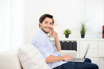 handsome and cheerful young man on sofa at home websurfing and shopping online with laptop computer and internet technology