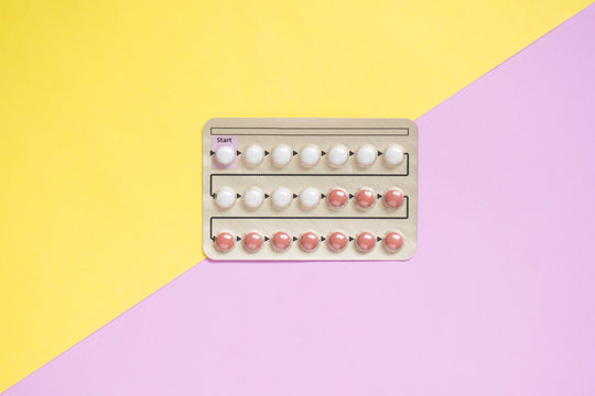Oral contraceptive pills blister on yellow pink background. Hormones used to prevent pregnancy and treat other medical conditions, such as PCOS, endometriosis, amenorrhea or acne. Gynecology concept.