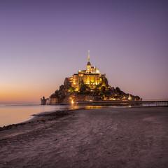 Mont Saint-Michel in abendlicher Stimmung zwischen der goldenen und der blauen Stunde. Mont Saint Michel in Nachtbeleuchtung.