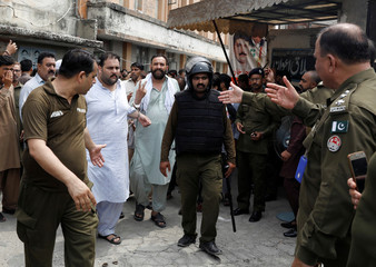 Supporters of PML-N who were arrested after holding a rally are handcuffed and escorted by police after they were appeared before district court in Rawalpindi