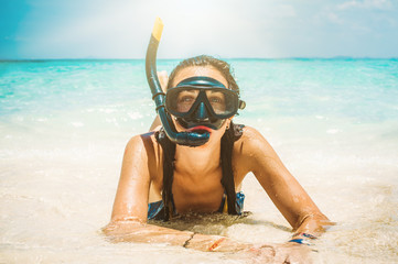 Happy young woman with snorkeling mask enjoying on the beach