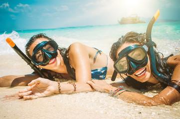Fototapeta Two happy girlfriends with snorkeling mask enjoying on the beach obraz