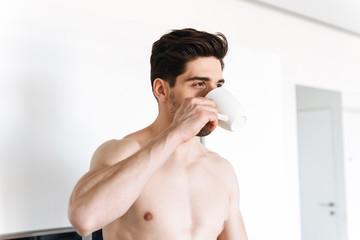 Handsome shirtless man drinking coffee