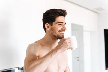 Happy shirtless man drinking coffee