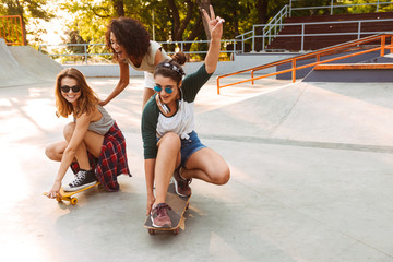 Three cheerful young girls with skateboards