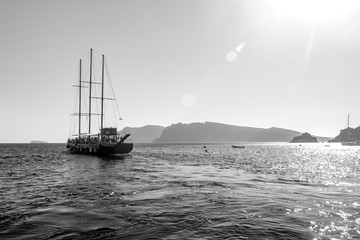 Tourist boat sailing away in Santorini, Greece. Amazing daytime view towards the Sun and deep sea crystal waters, bright black and white image with a lot of light