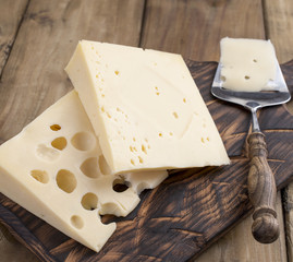 A beautiful Swiss cheese with holes, a useful dairy product. Tasty food. Country style photo. Place for text. Copy space.
