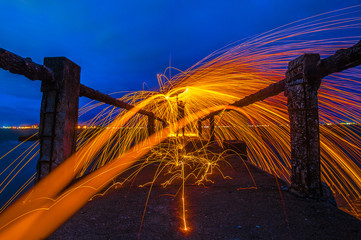 Showers of hot glowing sparks from spinning steel wool.Fire dancing show at twilight.Burning Steel Wool spinning. Hot Golden Sparks Flying from Man Spinning Burning Steel Wool on Wooden Bridge Extend