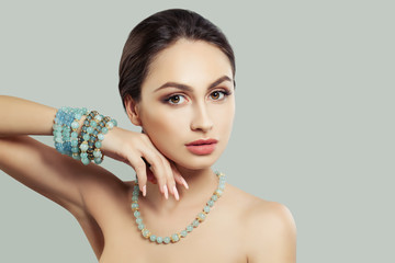 Attractive Young Woman with Makeup, Jewelry Necklace and Bracelet on Background with Copy space