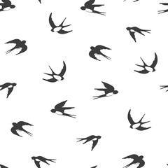 Flying swallows silhouettes. Black and white seamless pattern.