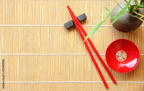 Red Wood Chopsticks And Red Bowl For Sushi On Bamboo Mat
