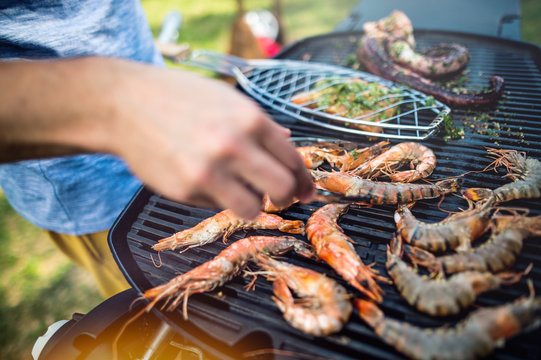 Unrecognizable man cooking seafood on a barbecue grill in the backyard. Close up.
