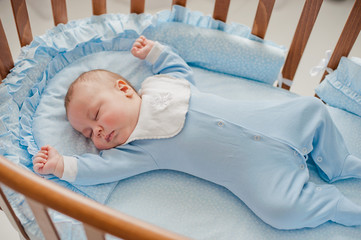 Baby's restful sleep. Newborn baby in a wooden crib. The baby sleeps in the bedside cradle. Safe living together in a bedside cot. The little boy dozed off under a knitted blanket.