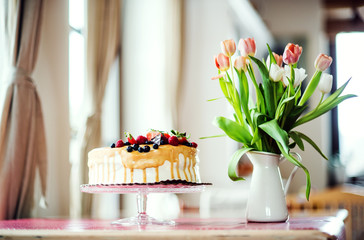 A birthday cake on a glass stand and a vase with tulips on the table.