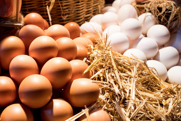 Chicken eggs of different sizes and colors on a table at a market. White and yellow eggs with hay and a wicker basket on the background.