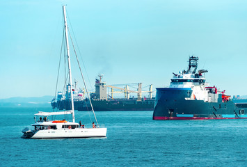 Freight ships and white yacht