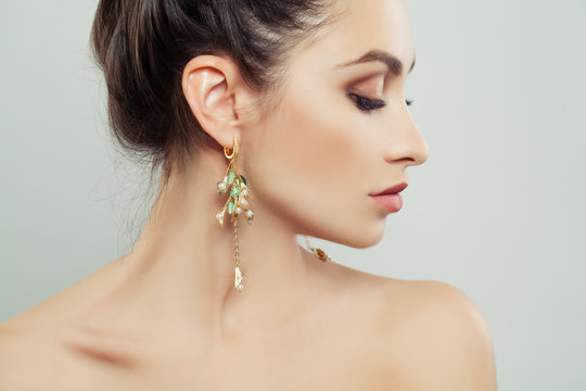 Attractive Woman wearing Gold Earrings with White Pearls and Green Gem
