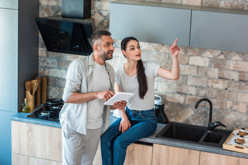 married couple with digital tablet looking away in kitchen, smart home concept