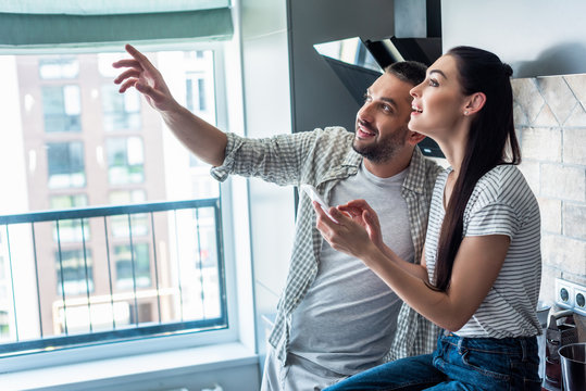 side view of smiling couple with smartphone looking away together in kitchen, smart home concept