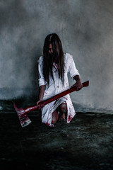 Ghost woman with bloody axe in her hand in the dark. nightmare, horror of scary fear on hell is monster devil in halloween festival, copy space the right.