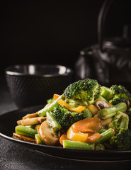 Hot stir fried vegetables on black plate. Healthy asian food concept with copy space. Toned