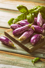 Heap of small eggplant or aubergine vegetable with basil leaves on old wooden background. Healthy food concept with copy space. Retro style toned.