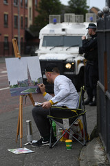 A man paints a picture as police watch over members of Loyalist Orders participate in Twelfth of July celebrations in Belfast