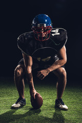 serious american football player standing on grass with ball and looking at camera on black