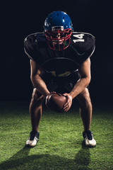 american football player standing on grass with ball and looking at camera on black