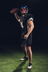 american football player on green grass throwing ball on black