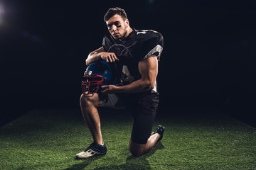 american football player standing on one knee on grass with helmet on black
