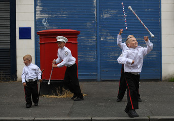 Young members of Loyalist Orders throw their batons in the air as they participate in Twelfth of July celebrations in Belfast