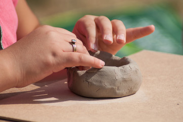 closeup of hands of child making clay pottery bowl  in outdoor