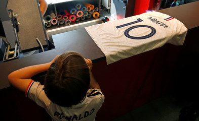 A child looks at an official France team soccer jersey with the name of soccer plater Kylian Mbappe at NSH Foot Store in Paris