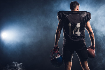 rear view of equipped american football player with helmet and ball in hands against white smoke