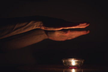 Sabbath Jewish tradition with candles on table and hands on top praying in the darkness. Vintage effect. Low key image