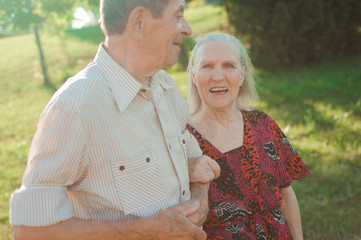 Age couple in love holding hands on a walk in the park in summer