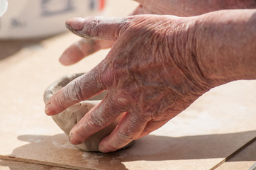 closeup of hands of old woman making clay pottery bowl in outdoor