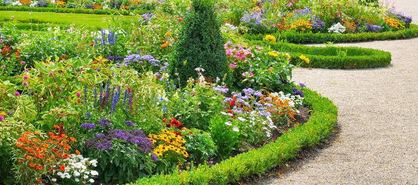 Lush flower beds in the summer garden.Wide photo.